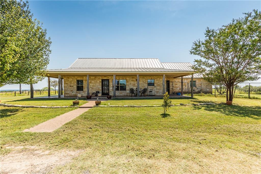 Interested in owning your very own slice of heaven in the country? Then look no further!! This property sits on approximately 41 acres of gorgeous land and has the most beautiful views of the country side! It is a horse ranchers dream with 10 separate fenced areas, a barrel racing arena, large shed with tons of storage, and a fantastic 4,560 sq ft horse barn with stalls! In addition, this property has an efficiency cabin near the horse barn that is equipped with a kitchen and bathroom which could be a guest house. The main home has wonderful rustic charm with a stone facade and wooden columns that line the covered porch that stretches around the majority of the home. This porch gives you plenty of space to take in the views from all around the property and enjoy the stunning sunrises and sunsets that you will get to take in everyday! Make some new memories while relaxing in the backyard entertaining guests or even soaking in the hot tub! When you enter the 2,054 sq ft home, you will be welcomed by a large open concept living, dining, and kitchen area. This space is very open and perfect for hosting holiday dinners. The split concert floorplan has two bedrooms and a bathroom to one side of the home with the master suite secluded to the other. The large master bedroom has its own door to the back patio and a huge ensuite bathroom. The bathroom offers his and hers sink and drawer space, two large walk in closets, soaking tub, and separate shower. This property really has it all and is ready for a new owner to call it home! Do not hesitate and call us today to see this breathtaking property in person!