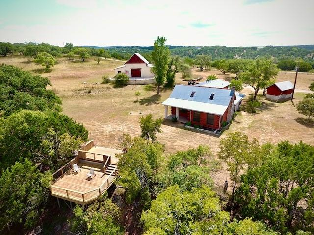A true one-of-a kind paradise! 22.77 acres with a beautifully remodeled 4/3.5 log & stone home sitting along a bluff overlooking your beautiful 2500+ feet of Sycamore Creek! Enjoy the scenery from the viewing deck or relax on the 1000+ square feet of patio off of the amazing Timber-frame barn Complete with electricity, plumbing, septic and propane. The two-story barn is a piece of art with it's mortise and tenon structure! Take note, there is no sheetrock in the entire home or barn, all natural wood and stone! Half of the acreage is cleared with grassy pasture and lovely oaks while the other half is wooded down to the rocky bottom creek with beautiful waterfalls and swimming holes! Minimal restrictions, bring the animals! Land can be further subdivided down to 4 acre lots per deed restrictions.