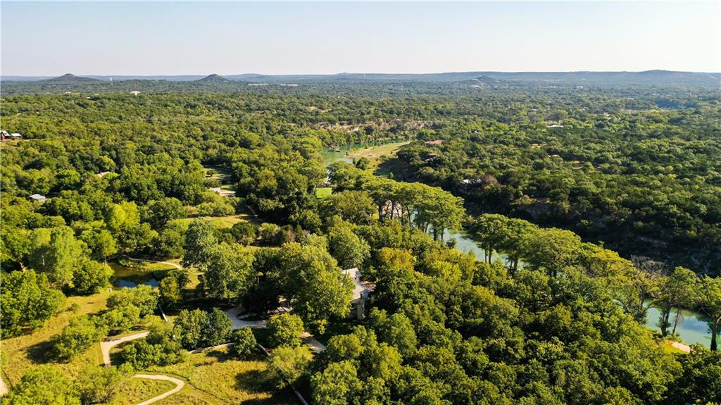 A treasured and exceptional sanctuary with over 700 feet of waterfront with shallow rapids along the deepest end of the Blanco River just moments from charming and artsy downtown Wimberley. Surrounded by groves of majestic Cypress, Cottonwood, Sycamore, and Pecan trees, this lushly landscaped estate offers three fishing ponds stocked with bass, catfish, tilapia, and perch, perfect for casting practice or catching a nice size bass for dinner. A mile of serene crushed granite walking trails winds through fields of native grasses and wildflowers that offer excellent bird watching and an annual migration path for the Monarch butterflies qualifying the property for a Wildlife tax Exemption. The main house and guest house were designed by award-winning architect Val Glitsch. With exceptional finishes throughout, the thoughtful design garnered an AIA/Houston Architecture Honor Award in 1998. Exposed wood trusses, tree-columns, and local limestone enclose living spaces with continuous rows of casement windows and doors to direct views and breezes through the narrow house down to the river. Long overhangs and deep porches allow interior spaces to open to the outdoors, even in the rainy season, and expand the livability of the interior spaces. The main house has 2 bedrooms plus a four seasons room, 2 full and 1 half bathroom as well as a two-bedroom, two-bathroom guest house with a partial kitchen and laundry. With 15 low-maintenance acres it offers the opportunity to expand on the property creating significant, additional value for the new owner. Enjoy it for year-round living or as an amazing country retreat. Put your personal stamp on this remarkable property, convenient to both Austin and San Antonio and interstate 35 and Ranch Road 12.