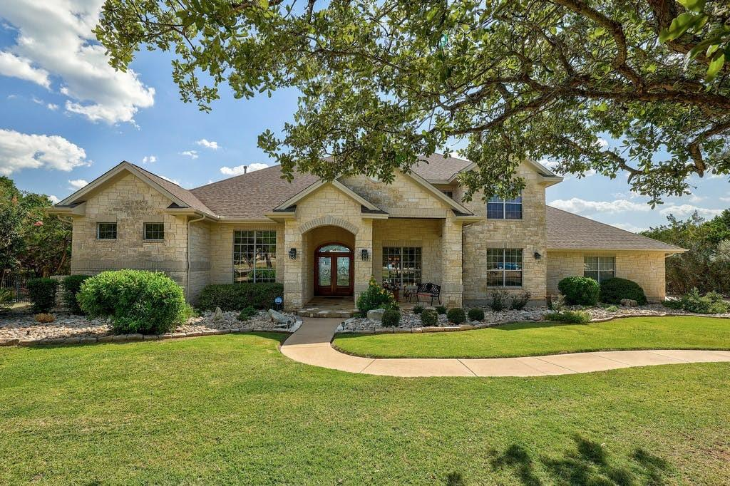 Beautiful custom home ideally set on a 2.9 acre corner estate in gated community of Grand Mesa at Crystal Falls. Spectacular views begin as you enter the home from the Texas Star inspired double front doors, large great room w/2 story ceilings, surround sound, crown molding, custom built cabinetry & FP mantel w/accent lighting & gas starter. Floor to ceiling windows allow tons of natural light & captures the Hill Country views. A cook's dream kitchen incl double ovens (convection & standard), warming oven, under counter microwave, granite counters, deep stainless steel sink & lre center island w/abundant storage. Relaxing breakfast area w/oversized windows overlooks pool. Large formal dining room off foyer has beautiful custom china cabinet/display case. Main floor primary suite w/custom drapery,  coffered ceiling, crown molding details & has it's own access to covered rear patio/pool. Luxurious primary bath boasts large dual head walk in shower, garden tub & large walk in closet w/custom built ins. Main floor study w/custom floor to ceiling bookcases & French doors. Main floor guest room accommodates a king size bed & has access to full bath. HUGE upstairs game room is open to main level below, has access to covered rear balcony w/tiled floor, wrought iron railing & views for miles. 2nd floor bdrm accommodates king size bed & access to full bath. Upstairs study has been pre-framed for easy 4th bedroom conversion. Custom pecan/hickory cabinetry throughout entire home. Gorgeous high end COREtec vinyl flooring just installed on main level. Outdoor features include in-ground pool w/beach entry, spa w/water feature, multiple covered patios w/native stone decking, built in gas grill & surround sound, all in a private setting. Three car garage w/motion sensor lighting, built in peg tool storage, cabinetry & ramp entry to house for wheelchair access. Aerobic septic updated 2020. Three AC units, security system, sprinkler system & wrought iron fencing complete this home.