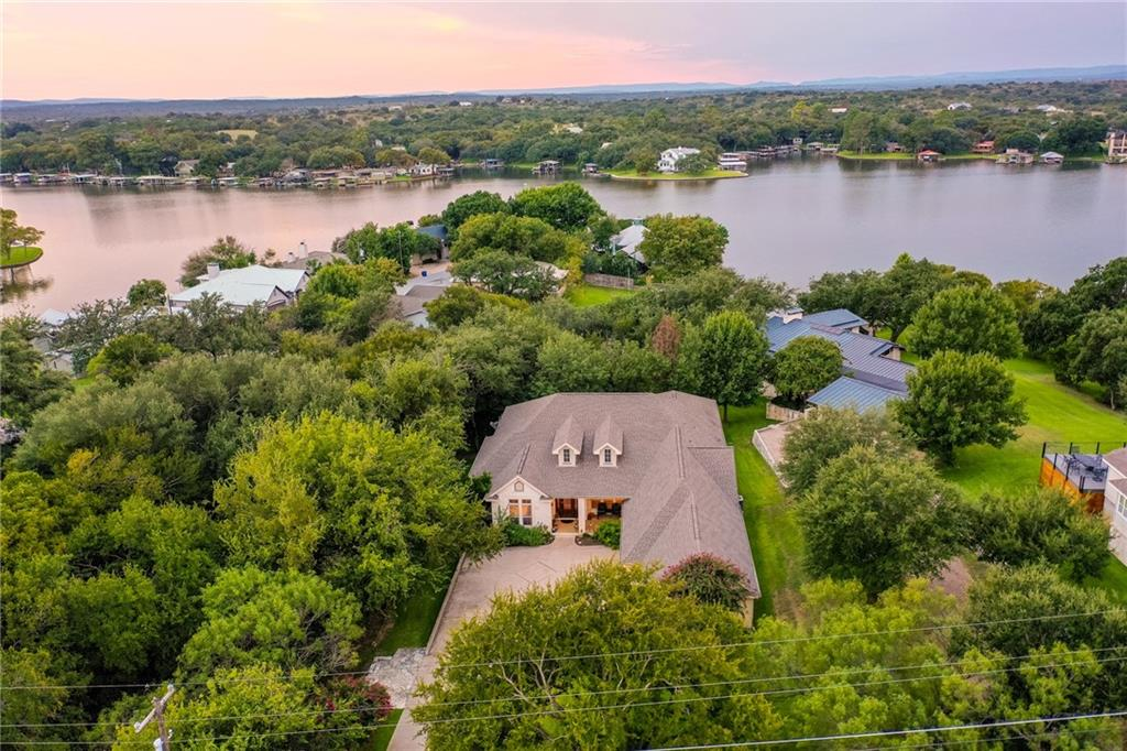 One-owner, custom-built, single story home in Blue Lake Estates on Lake LBJ. Approx 3500 Sq. Ft. of open floor plan with tall ceiling sand big windows, 4 spacious bedrooms all currently with King-sized beds, with 4 full baths, plus office and 3 car garage with work shop area and additional storage. This rare find was built as a primary residence overlooking the gorgeous, tree-studded backyard with gentle slope down to 85 feet of cove-protected water just off the Sandy Arm of Lake LBJ. You will love the huge, covered patio that spans the width of the house and overlooks the gorgeous property; the perfect spot to fire up the grill while enjoying your favorite drink. Lush green grass and beautiful trees make for the perfect yard to spread out and enjoy Lake Life in this super private and unique setting inHorseshoe Bay, Texas. Blue Lake Estates is one of the most desired communities on LBJ known for its rolling green lawns and the BlueLake 9-Hole Golf Course at the center of the neighborhood. This is the closest part of Lake LBJ to Austin and San Antonio, just offHighway 71 and very close to Baylor Scott & White Hospital. Good square footage like this, all on one level in a great neighborhood is extremely hard to find. 3402 Pack Saddle is a real gem in the ideal location in the Texas Hill Country. Come see for yourself!