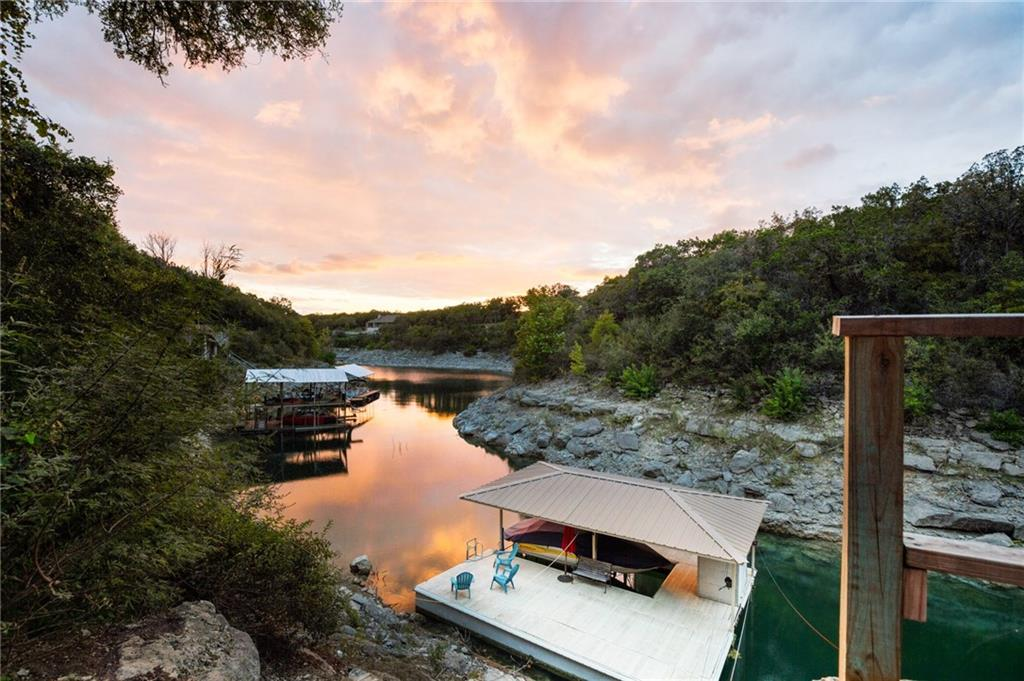 Amazing Lakefront Cottage on Lake Travis! Charming 2BD/1BA/1000 Sq Ft waterfront cottage with its own private floating boat dock on a deep cove (Mack's Canyon). This home is perfect for a weekend getaway, STR, and enjoying the outdoors. Incredible .41 Acre property with expansive back deck, flat backyard, and enchanting courtyard for extra dining under the stars. Walk down the steps to your own boat dock. Enjoy majestic sunset views from the private lake overlook deck. The boat dock features a boat lift, storage, and room to lounge on the dock. Lovely interior with vaulted ceilings and exposed wood beams. The living room features the original stone fireplace. The kitchen opens to the living room and offers breakfast bar seating, stainless appliances, and sleek granite countertops. The primary suite offers access to the backyard and a fireplace for cozy evenings. Convenient storage shed in the carport and detached laundry/ storage closet. Enjoy sunset dinners on your gorgeous patio or take visiting guests out to the nearby Oasis. Spoil yourself with a spa day at the close by Miraval Austin Resort & Spa. Less than 2 miles to Volente Beach Resort and Waterpark. Just 40 minutes from Downtown Austin in traffic. Nearby shopping, dining, and entertainment with easy access to 620. Less than 20 minutes to the Lakeline Mall and north Austin Tech Corridor.