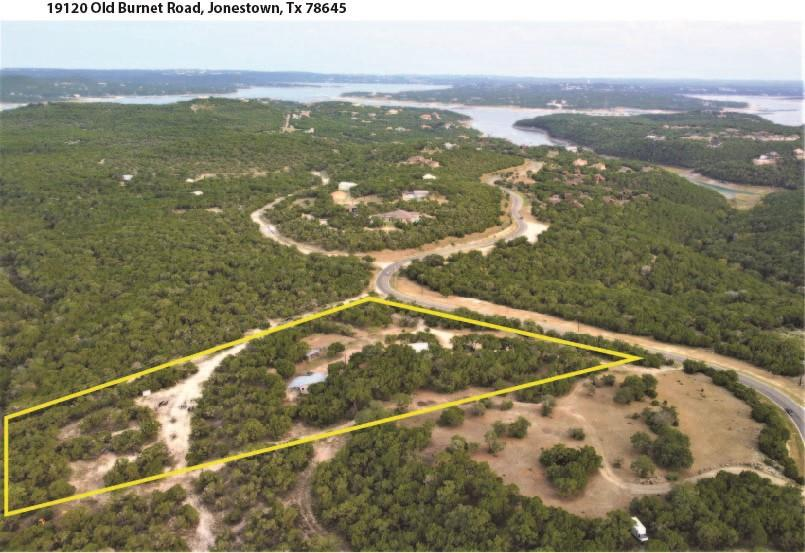 Panoramic Views! Awesome HILLTOP property located between Jonestown and Lago Vista inside The Hollows at North Shore Lake Travis.  This very private 6.6-acre property is a GEM with 180-degree panoramic views of the Texas Hill Country. Farmhouse style home is over 1,700 sq ft, boasting a 576 sq ft front porch and attached open deck has east, south, and west gorgeous views making morning sunrise coffee and evening sunset happy hours breath taking. Two bedrooms, two full baths, cathedral style living area open to the kitchen with dining area and a beautiful sunrise view. The large master bedroom leads down to a large master bath with jacuzzi tub, an extra-large FLEX room as an extra bedroom, office/studio. And a guest room with a view of the Hill Country and a private entrance! This MUST SEE property also features a detached, oversized two-car garage with a separate LARGE workshop, and a concrete RV Site Pad 50amp service. Property is on Jonestown city water, onsite Aqua-safe septic system with recent maintenance. All NEW AC/Heat unit, water heater, windows, porch ceiling fans, flooring throughout and completely painted interior!! PLUS, this property, by the roadside, has a golf cart/biking/hiking trail 16 miles around the community, to the Beach Clubs with pools, lakefront access, playground, fitness center. The Hollows' Community Social Membership provides access to The Hollows amenities for an annual fee. This property is an excellent opportunity with many options! Perfect for a primary residence, MULTIPLE residences (build your dream home) with an existing guest home, or as investment rental property! NO city or HOA restrictions, and a low tax rate of 1.8%. Located just half-mile from Lake Travis and minutes from Lago Vista shopping and dining spots. Jones Brothers Park with waterfront access and two boat ramps is ten minutes, Cedar Park is fifteen minutes, downtown Austin is a forty-minute trip. Don't miss this rare chance to Live the Texas Hill Country Lake Life!