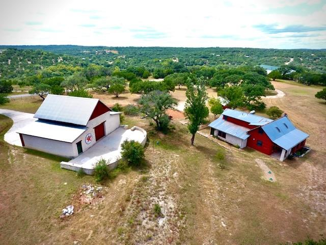 A true one-of-a kind paradise! 10.9 acres with a beautifully remodeled 4/3.5 log & stone home sitting along a bluff overlooking your beautiful 500+ feet of Sycamore Creek! Enjoy the scenery from the viewing deck or relax on the 1000+ square feet of patio off of the amazing Timber-frame barn. The two-story barn is a piece of art with it's mortise and tenon structure! Take note, there is no sheetrock in the entire home or barn, all natural wood and stone! Half of the acreage is cleared with grassy pasture and lovely oaks while the other half is wooded down to the rocky bottom creek with beautiful waterfalls and a swimming hole! Ferns and tons of animals can be found along the spring-fed portion of the creek! The two owned lots (8&9) can be joined or separated and even taken down to 4 acre lots per deed restrictions.