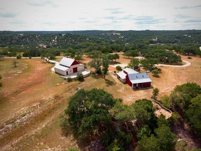 A true one-of-a kind paradise! 10.9 acres with a beautifully remodeled 4/3.5 log & stone home sitting along a bluff overlooking your beautiful 500+ feet of Sycamore Creek! Enjoy the scenery from the viewing deck or relax on the 1000+ square feet of patio off of the amazing Timber-frame barn. The two-story barn is a piece of art with it's mortise and tenon structure! Take note, there is no sheetrock in the entire home or barn, all natural wood and stone! Half of the acreage is cleared with grassy pasture and lovely oaks while the other half is wooded down to the rocky bottom creek with beautiful waterfalls and a swimming hole! An additional 11.87 Acre adjacent lot (8), can be bought together or separated and even taken down to 4 acre lots per deed restrictions. Short Term Rentals allowed!