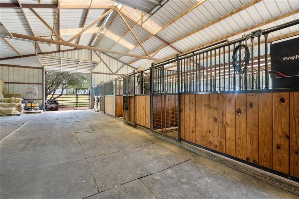 Own a piece of the beautiful Texas Hill Country, with 360-degree panoramic views in the gated community of Granite Ridge. 45-mile vistas also provide gorgeous views of Lake Travis. This 21-acre property includes a round pen, 94x200 horse arena, an impressive barn with tack room, four 12x12 stalls, and room for up to twelve 12x12 stalls and paddock areas. The acreage is fully fenced with a security gate and cross fencing for three large pastures. A leveled building site with miles of panoramic vista views is the perfect place to erect a custom dream home. Also featured on the property is a spacious and light-filled two bedroom, one bath guest house. The cozy home offers a wrap-around porch for relaxing and enjoying the fresh air and stunning views. Stainless steel appliances, granite counters and recess lighting. A low tax rate and wildlife exemption are added bonuses to keep expenses low for the owners. This Hill Country property is just a 20-minute drive to the Hill Country Galleria with great restaurants/shopping and 30 minutes to the award-winning Texas Wine Country.