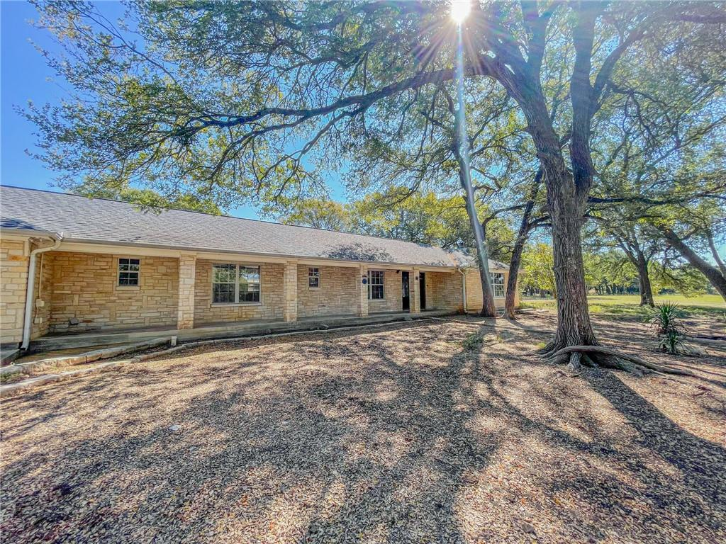 """Hidden gem with TONS of potential! 3100+ sq. ft. with 3 beds, 2.5 baths, 2 living areas/flex space, 2 wood-burning fireplaces, in-ground pool, and courtyard. Nothing """"cookie-cutter"""" about this home! It's a """"U-shaped"""" layout and is truly unique! This home has 7 exterior doors, which include 4 walk-outs to the courtyard and one walk-out from the master bedroom """"sitting"""" area that leads to the back patio and in-ground swimming pool! Masonry is complete for an outdoor kitchen, as well! Circle driveway, fully fenced backyard (privacy and goat fencing), tons of beautiful Oak Trees, and some fruit (peach) trees in the front! This home sits on 2 acres and is on a well and septic. There is also a 12x12 storage shed in the backyard. RV hookups in the front of the home, as well. You HAVE to see this home to appreciate the potential."""