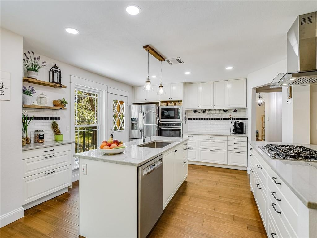 INCREDIBLE LOCATION across from the North Austin Tech Corridor. This refreshing greenbelt home is a natural urban oasis with a huge tree-filled nature lover's backyard featuring a creek & waterfall, after rain. This gorgeous 3BD/2.5 BA home features a stunning bright interior with vaulted ceilings, exposed wood beams and pristine hardwoods throughout. Fantastic open concept kitchen-dining room-great room and access to a fenced-in patio area. The great room features a cozy wood-burning fireplace nestled in a floor-to-ceiling white limestone hearth. A secluded second living/office/flex area on the main floor offers access to a second patio area. Stunning gourmet kitchen fully renovated with custom kitchen cabinetry (full drawer units below), natural stone (quartzite) countertops, center island, Bosch dishwasher, built-in oven (new 240V circuit for the wall oven), oversized microwave, 5 burner gas cooktop with wok-burner and chef's range hood. The owner's suite serves as a peaceful getaway and offers access to a spectacular oversized deck with picturesque views of the creek, green space and neighborly deer. Luxurious ensuite bath with updated quartzite countertops and Travertine tiles in the walk-in shower and walk-in closet. This home has been beautifully remodeled with updated windows & siding (both with limited lifetime warranties), updated appliances and an updated water heater! Well maintained furnace and HVAC (approx. 5 years old). The backyard is very private with only one close-by neighbor. Two-car garage with workbench space. Dusk-to-dawn LED lights up front (garage wall and entryway). Basic dusk-to-dawn light at the back porch. Existing underground sprinkler system (currently disconnected at waterline). Great Hills Park trailhead is only 0.3 miles away. Less than 10 minutes drive to major employers along 183 and at the Domain. Incredible shopping (Trader Joes, Whole Foods, HEB), dining and entertainment nearby in all directions. 20 minutes to Downtown Austin.