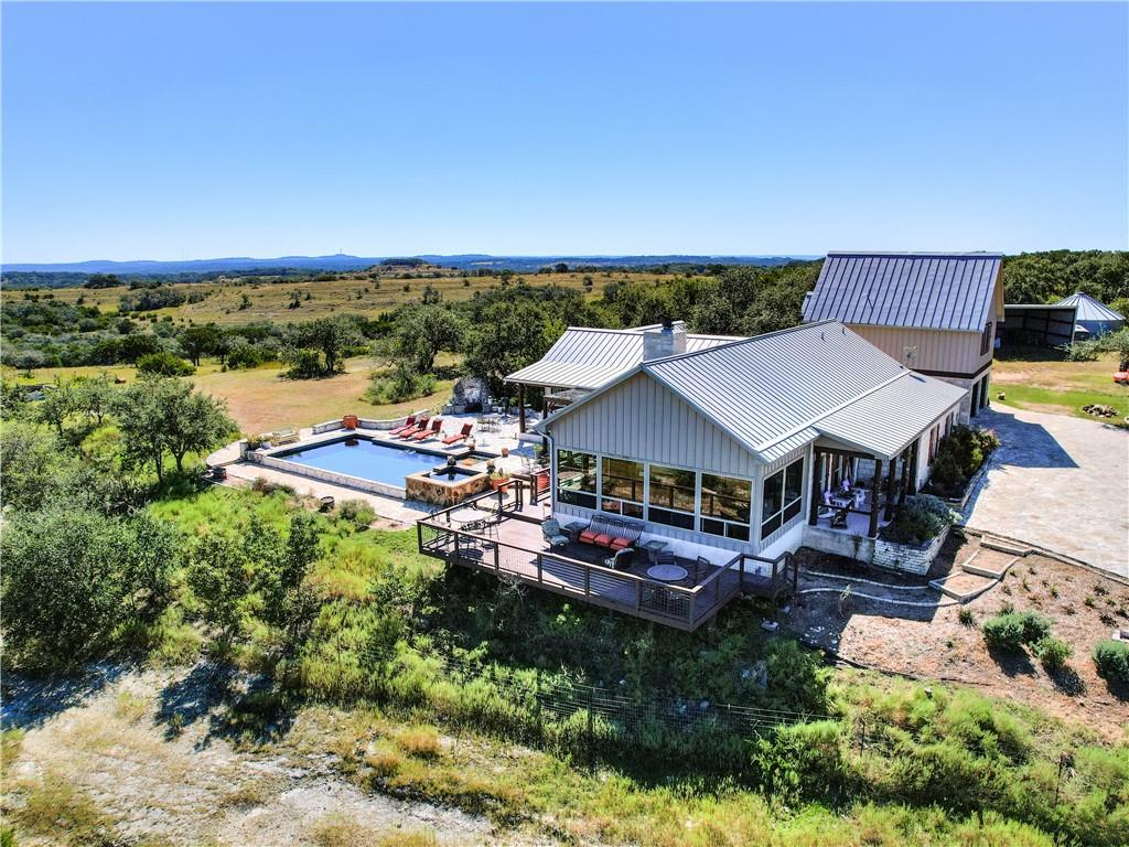 """Secluded and Private. One of the highest elevations in Hays County, this property has breathtaking panoramic views of the Hill Country, with beautiful madrones, cleared pastures, and a grotto in the bottom land.  Many structures and features on the high point of the property, including a main residence that was remodeled with high-end finishes, and custom in-ground negative edge swimming pool. A detached """"mother-in-law"""" suite with full kitchen and surrounded by peach and fig trees. A studio apartment above the garage. A free standing """"Morgan"""" building currently used as an office, A fenced in vineyard, a 50'x30' barn, a rainwater collection systems that feeds into a 30,000 gallon water tank, a propane fueled generator, and a fenced in goat pen. The property is fenced, cross fenced and gated. Because of the high elevation of the property, the internet has a line-of-site signal and is very strong."""