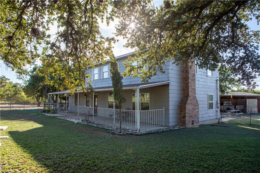 INVESTOR SPECIAL!  An incredible opportunity to own Hill Country acreage, only 30 minutes from Austin. Three acres of unrestricted, prime real estate nestled between mature trees minutes from commuter train station, hospitals, dinning and shopping (approx. 3 miles). The two-story home features a beautiful brick, wood-burning fireplace. Exterior features include an extra spacious covered front porch overlooking the front yard and an uncovered patio in the backyard. Updates to the second level include new wood-like vinyl flooring, fixtures, new interior paint and new roof installed in 2016. There are 2 living structures on this property, the main house and the guest house; the guest house has 3 bedrooms and 1 bath. Plenty of parking including an oversized three car detached carport. Also parking for trailer, RV, or boat. Residential and/or Commercial opportunity!