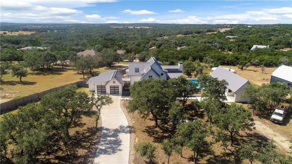 Back on market due to buyer financing. 151 Terra Scena Trail is a recently completed & highly customized 4 bedroom/3.5 bathroom Modern Eco-Farmhouse w/ a spacious pool, spa, and full guest house (added by original owner) situated on over an acre corner lot w/ towering live oaks & natural landscaping. Perfectly located in between downtown Dripping Springs & Bee Cave within the sought after Terra Scena community w/ 9 acres of private trail access, this home offers ample space, privacy & hill country views while still being accessible and connected. The main home is a standout w/ wide-plank white oak flooring & natural light, featuring custom automated window treatments throughout the home. The living & entertaining space on main level is accented by super-high ceilings w/ a native stone fireplace facade built to the very top. The primary suite on the first floor contains ample closets, a double vanity & a soaking tub & rainwater shower. The outside flows effortlessly into the interior w/ the massive pool & separate spa just steps away that is plumbed for an outdoor shower as well. Adjacent to the pool & spa, the guest house encompasses not only a full bedroom and bathroom, but is plumbed for a kitchenette (installed shortly) & living space as well as lofted living space above so that your guests feel at home & taken care of in their own space. The connected garage will not only allow two full-size cars, but also can be accessed by a side-loading bay with an attached workshop. The entire property runs on rainwater collection (30K gallon tank) & is optimized to be extremely energy efficient and eco-friendly, w/ all electric on site, including an induction range, solar and EV pre-wiring, multi-zone optimized HVAC, and more. A very short drive from the Hill Country Galleria and all of the incredible new restaurants & entertainment including Fitzhugh Rd. breweries, distilleries & wineries.