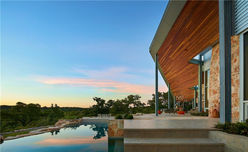 A once in a lifetime opportunity awaits at Backbone Ridge Ranch, one of Wimberley's most iconic and pristine properties. With its highly coveted location, Backbone Ridge Ranch is just minutes from downtown Wimberley – the Hill Country's epicenter of arts, gastronomy, and culture. A private hillside paradise, this iconic estate is nearly 50 acres with a mix of dramatic vistas, golden meadows, seasonal flowing water, and breathtaking ridge lines. The additional adjoining 50 acres are available to purchase as well. This versatile property creates the complete package for the discerning buyer in search of a move in ready, low maintenance private estate & ranch with unparalleled scenic views, wildlife, and nature on a grand scale. The 4,369 SQFT main home offers 4 en-suite bedrooms, including the primary suite. Enjoy the outdoors from the comfort of the outdoor living area complete with a kitchen, dining area and fireplace all overlooking the sparkling pool. Once again maximizing the connection to the surrounding countryside, the quarried limestone creates a gentle edge to the oversized 33,000-gallon pool. Multiple raised vegetable garden beds offer fresh produce for the gardener enthusiast or chef! A one-acre fence surrounds the home. Two separate 3 car garages offer additional space for car enthusiasts. Above each garage is a 487 SQFT private residence, complete with a full bathroom and well-appointed bedroom with extra sitting space, ideal for multi-generational living, or a live-in nanny. Following LEED principles, the estate boasts 84 solar panels, rough-in electrical for 3 Powerwall Batteries, 24,000 gallon rainwater storage system, 6 Rinnai tankless water heaters, and LED lighting throughout. This property is 45 miles to both the San Antonio and Austin airport, 10 minutes to downtown Wimberley, 15 to San Marcos, 10 minutes to Canyon Lake, and 20 minutes to New Braunfels. Enjoy the luxury of true privacy only minutes from the conveniences of town.
