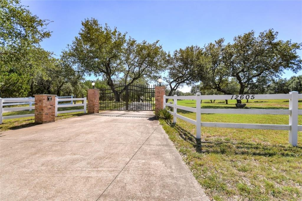 Beautiful and private!  10.237 acres within thirty minutes of downtown Austin.  Panoramic views of the Hill Country.  Perimeter fenced with remote gate entry.  Paved driveway leading to the perfect five bedroom/three bath home on the hill surrounded by towering oaks and inviting porches to enjoy the breeze and the view. A wet weather creek runs through the property and feeds the pond.  This property is unrestricted so bring your imagination and envision a wedding venue, a corporate retreat, a bed and breakfast, or bring your horses.  Perfect for the hobbyist who enjoys restoring vintage cars:  the oversized metal building already has the car lifts in place and can accommodate several cars!  Plenty of parking for almost any kind of event.  Eight hundred foot well; Aerobic septic system.  Truly unique.