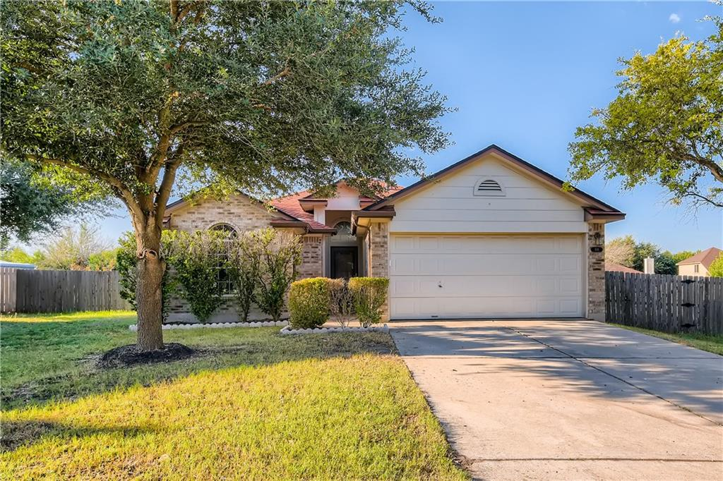 You will feel right at home in this 3 bedroom, 2 bathroom home on a cul-de-sac across the street from Hutto Lake Park! Upon entry, the sleek wood-like flooring opens up into an expansive living area featuring a tiled fireplace and fashionable ceiling fan. The attached horseshoe-style kitchen features a gas stovetop, vaulted ceilings, and ample storage space. Relax in the comfort of your primary suite, boasting a walk-in closet and an en suite bathroom with a dual sink vanity, soaking tub, separate shower, and chevron style flooring. Entertaining is a breeze with the covered patio in your fully fenced backyard! Don't miss out on this location close to schools, shops, TX-130, and The Golf Club at Star Ranch.
