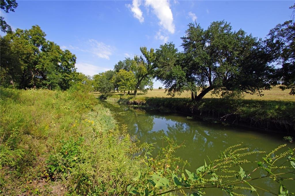 Beautiful, hill country, 14 AG EXEMPT acres on Clear Creek in Liberty Hill. The property has good tree cover that includes oaks and pecan. Pastures have native grasses, black and caliche soil with a level to gently sloping topo. There's also one stock pond. The east boundary is the center of Clear Creek. A dam on neighboring property creates deeper water in creek on this property. A great property for livestock, horses, family recreation and building your dream ranch home. Access is by deeded easement also used by two other property owners. PEC electric is at the county road. A well and septic would be required. Neighboring wells range from 510' to 610'. Several internet options and a neighbor said they are happy with SOS Communications. Archery hunting is allowed but recreational firearm use is not per the deed restrictions. In Burnet ISD.