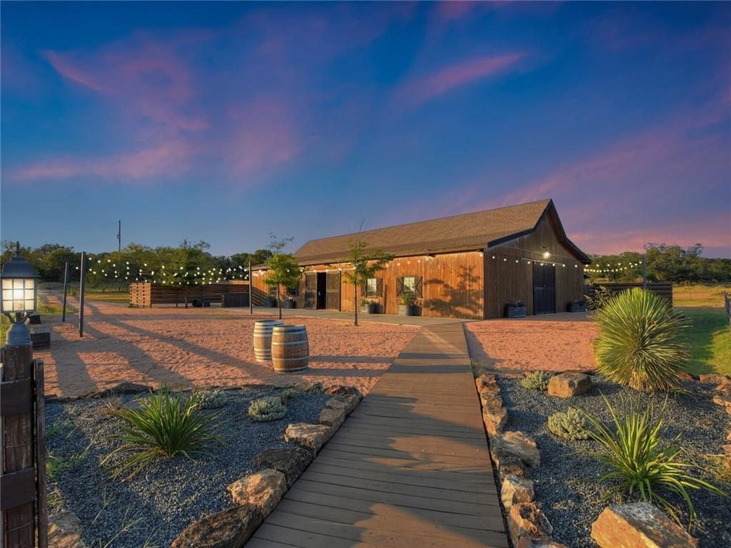 """A unique opportunity awaits at The King River Ranch, roughly 25 flat, manicured acres that gently slope to 1,000 feet of the Pedernales riverbank that was once home to Native American villages dating back thousands of years. Tranquility and harmony coexist on this private ranch complete with the original farmhouse, detached guest house, reception barn, animal barn, and stocked fishing pond. The King River Ranch is currently a successful event and wedding venue conveniently located in the heart of Johnson City's corridor of vineyards along the 290 Texas Wine Trail that starts right down the road and continues into neighboring Fredericksburg. This spectacular property embodies all that is the Texas Hill Country with the serenity and privacy of ranch living and the bonus of easy access to town, wineries, breweries, shopping, art galleries and much more. The 4-bedroom, 3-bath original farmhouse is over 3,000 SF with two separate living areas, a full kitchen and a screened porch where guests can kick up their feet and enjoy the Hill Country sunsets. The charming studio-style guest house has a kitchenette, a soaking tub and two salon chairs for wedding hair and make-up – the perfect place for a bride to get ready for her big day. Couples will enjoy their first dance in the stunning """"rustic chic"""" barn where beautiful chandeliers provide a romantic setting. Continue fulfilling the dreams of happy couples by building upon this impeccably rated 5-star venue space, or let your imagination run wild – vineyard, distillery, family getaway or desirable short-term rental – the sky's the limit! Don't miss the opportunity to own this stunning one-of-a-kind property. The land has an existing agricultural exemption and all the friendly animals – horses, sheep, donkeys and even an affable goose – convey. https://ownkingriverranch.com/"""