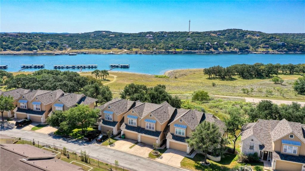 Lake Travis Waterfront Living at a fraction of the cost! Waterside Oaks is a Gated Waterfront Condominium Complex located at the end of a cul de sac on the shores of Lake Travis. Enjoy the private amenities of the complex as well as the Lago Vista POA Amenities. This middle unit backs to the waterfront park and is adjacent to the pool. Recent partial renovations are; new granite installed in the kitchen, freshly painted cabinets throughout, new quartz counter tops in the 3 baths, no carpeting, new laminate throughout and hard tile installed in the kitchen and half- bath. Various new gold brass lighting and hardware installed. A/C is less than 2 years old. Mandatory membership in the LVPOA is for an additional $150/ yr. Short term rentals not allowed.