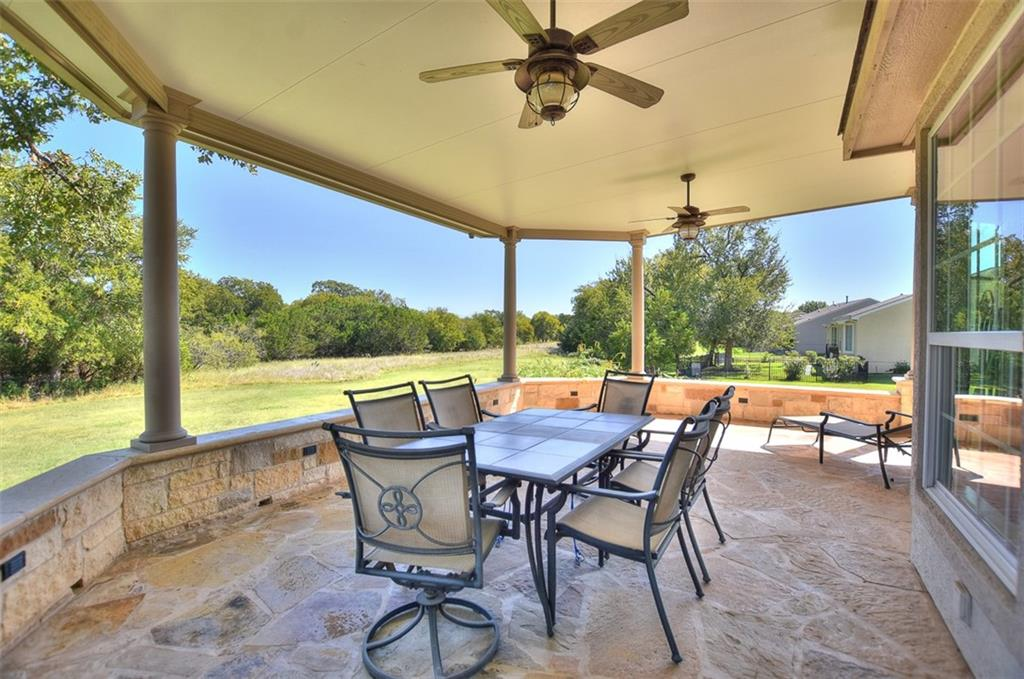 With a greenbelt both beside the home and behind it, this one-of-a-kind Sun City Texas DeLeon greets you with a wide driveway hosting an over-sized Three-Car Garage.  A large stone courtyard leads to the entry, where off the Rotunda Foyer resides a Study/Computer Room, an ideal Office-at-Home.  Steps away are a well-placed Powder Room and a Laundry brimming with storage. The tile floors that begin at the entry blanket all of the home, but the sleeping quarters.  The ceiling raises to ten feet in the sizable Great Room, off of which a separate Formal Dining touts triple windows viewing the private side yard with adjacent greenbelt.  The Open Kitchen is flanked by the before-mentioned Formal Dining and a bayed Breakfast Nook viewing the woodsy banks of Berry Creek.  A fun Menu Desk at the Nook also boasts a superior view.  Plentiful cabinets and an easy-care Corian counter top circle the Kitchen anchored by a corner Walk-In Pantry.  Quietly located a the rear of the home, the kind-sized Primary Bedroom flaunts fabulous views of the scenic back yard setting, where a just a tiny portion near the property line is actually located in the 500-year floodplain.  Meanwhile, the en suite Primary Bath offers dual vanities, a soothing jetted tub, a spacious shower, a generous Walk-In Closet, and a jumbo Linen Closet!  The open Game Room makes an ideal Hobby Area, Media Room, or Quilting Retreat.  Privately situated at the front of the home, Two Guest Bedrooms flank a Jack & Jill Bath.  But, the heart of the home is the incredible Patio area, where an added Patio adjoins the original Covered Patio creating a shady, custom outdoor retreat like no other.
