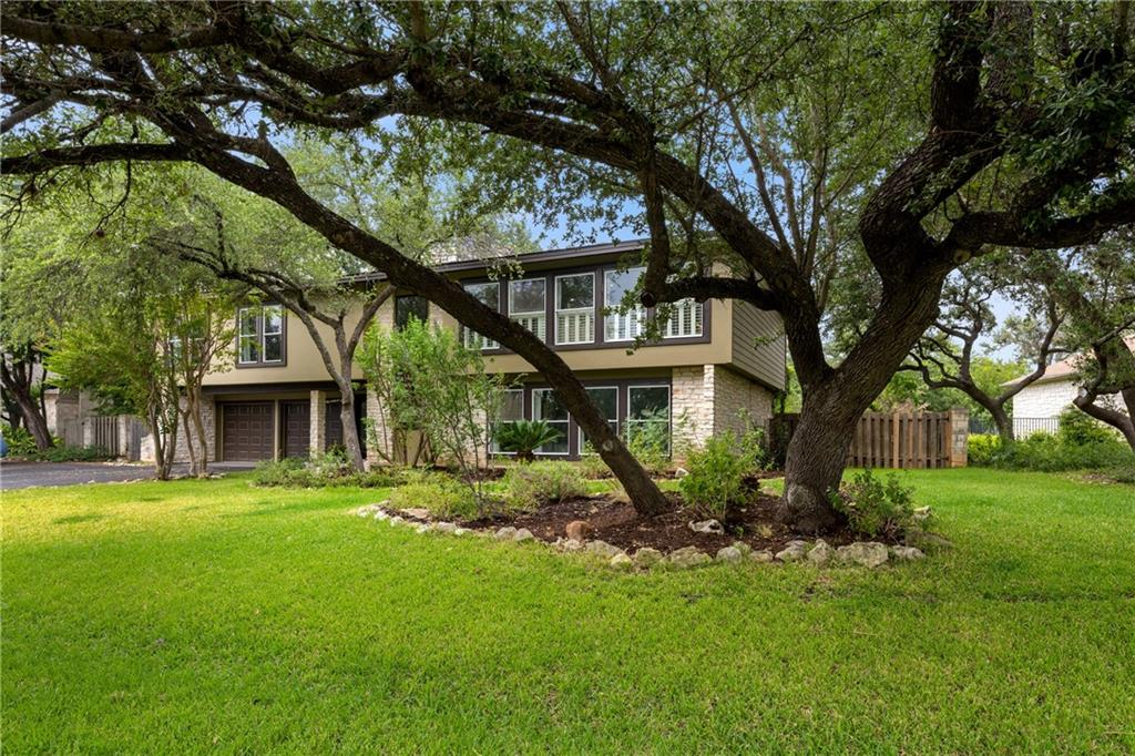 Pride of ownership shines in this tastefully remodeled Midcentury style family home just minutes from Lake Travis! A 3130 sq.ft home is presented on a .289-acre lot under a canopy of majestic trees in historical Lakeway proper! A modern staircase & stone wall welcomes the entry & leads to the second floor where you'll find the main living areas, owner's suite & two secondary bedrooms. A dramatic living room boasts walls of picturesque windows & plantation shutters and a floor-to-ceiling stone fireplace that provides comfort and warmth during the wintertime. Gorgeous hardwood flooring flows from the living room into the dining room complete with a beautiful light fixture and glass panel french doors that lead to the back deck. A breakfast bar wraps around the chef's complete remodeled kitchen appointed with sleek modern cabinetry with custom pull-out drawers, stained butcher block countertops, an apron sink, a center island with a stunning concrete countertop, and high-end appliances. The owner's suite features a private deck,fabulous walk-in closet, a recent remodeled spa-like en-suite bath,double vanities, an oversized walk-in shower, a jetted tub where you can soak with a glass of wine. Two spacious secondary bedrooms w/ hardwood flooring and a full guest bathroom complete the upper floor. A large den is located on the lower floor where you can entertain family and friends. The den offers plentiful natural light and another wood-burning fireplace. The fourth bedroom is located on the lower floor near the second remodeled guest bathroom and is perfect for the college kids or nannys qutrs!A spacious backyard for outdoor living features a large deck where you can lounge or grill, a lower patio, plenty of green space for kids & pets to play w/ mature trees that provide excellent shade and privacy. Take a quick stroll to the cul-de-sac to view the lake. Lake Travis Schools/near Rough Hollow Marina/Lakeway Inn & Marina and Spa,4 golf courses, community swimming pool!