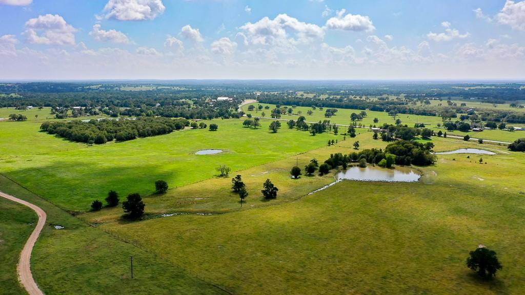 This 109 acres is located 15 MILES FROM ROUND TOP, 25 miles from Bastrop, and 4 miles from Downtown Giddings! Don't wait to check out the BEAUTIFUL VIEWS this property has to offer. With 4 ponds, plenty of mature trees, and a sloping terrain, you will find many potential building sites throughout the property.  It is fully fenced with electricity and water available.  It includes a metal barn with cattle pens and a large shed for equipment tucked into a bundle of trees. Take a day off to relax and fish for catfish, trout, perch, and bass. This property has approximately half a mile of road frontage on FM 2239.