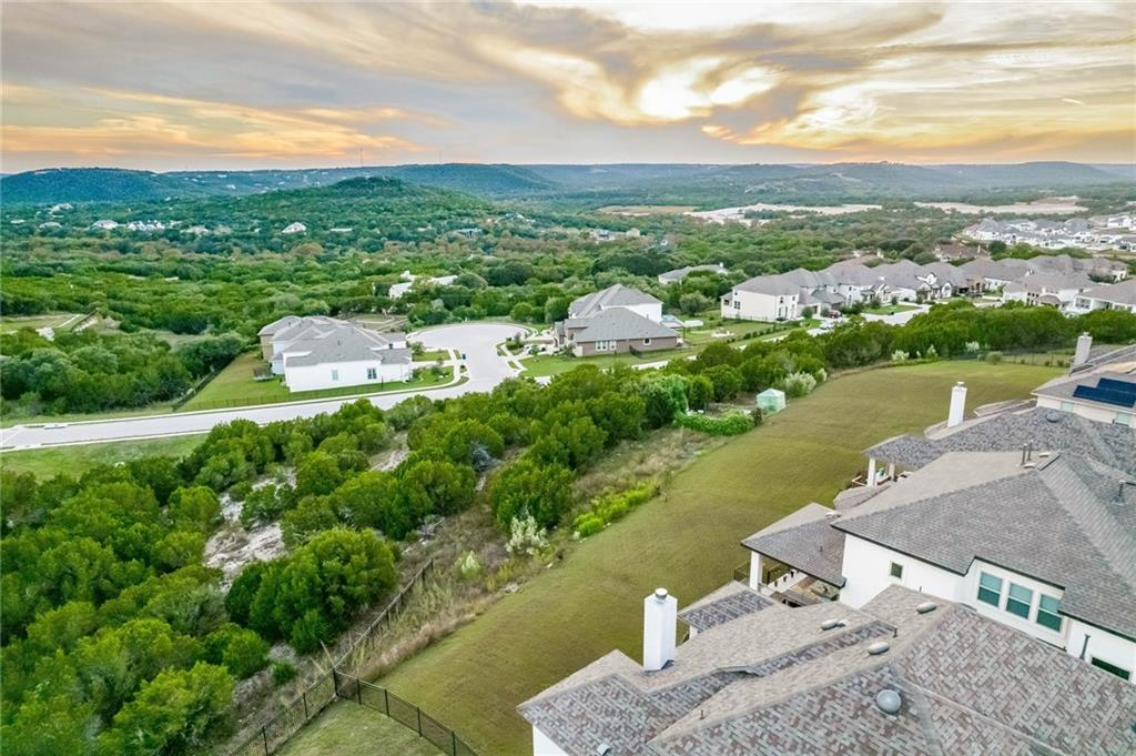 Meticulously maintained, gorgeous home with tons of upgrades located on top of a hill with stunning hill country views! You can see for miles right from the back covered patio and from inside the home in many rooms! The primary bedroom, primary bathroom, an additional bedroom, additional full bathroom, and a dedicated office with glass French doors are on the first floor. This spacious home boasts many custom touches including high ceilings throughout with a soaring ceiling in the living room, luxurious engineered hardwood flooring throughout most of downstairs, 8 foot doors, a stunning kitchen that is open to the living room with white cabinets, a stone backsplash and gray expo silestone countertops, a 240v electric car charger in the garage, gorgeous bathroom choices with piedrafina counter tops and rectangular undermount sinks, iron staircase balusters, white cabinetry, modern light fixtures throughout the home with tons of natural lighting  and so much more. The front yard has lush landscaping with river rocks in the flower bed with stone boarders around the trees, a spacious backyard with and a large, covered patio to enjoy the wonderful hill country view! There are no direct neighbors behind or to the left side of the home. The pride in ownership shows and you must see this gem of a home. Wonderful location that is close to shopping, entertainment and the Jones Brothers Park where you can launch your boat or just enjoy the lake. Located in the prestigious Travisso neighborhood with some of the best amenities offered including a resort-style pool with children's splash pad, pavilion, fire pit, two lighted tennis courts, a playground, recreational fields, open-air pavilion, clubhouse, fitness center, trails and more. It is all you could ever ask for in a home and community!