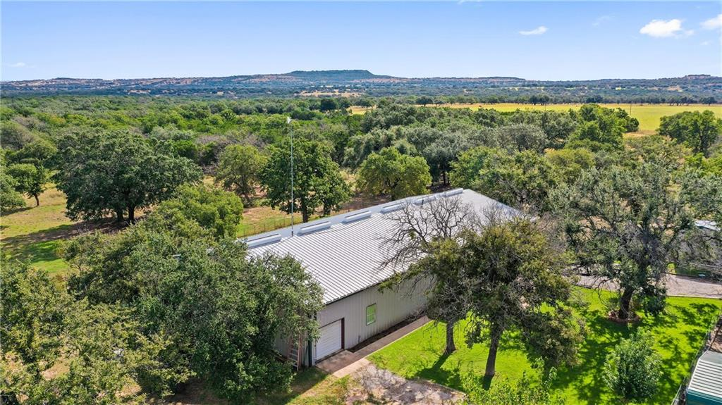 18+/- Unrestricted Acres!  This stunning property offers ultimate privacy with the luxury of being close to several awesome city's/towns.  The trees on the property are absolutely stunning offering an abundance of large live oaks and several other native trees.  The access to the property is great with over 840 ft of frontage on paved Lincoln Smith Rd.  There is a 5000 sq ft metal building on site that offers both shop and storage areas along with a 7 bed 3 bath home built inside.  The living space has a few projects left in order to be 100% finished but is currently livable. There is a great water well on-site and power and septic are in place.  Some of the cedar has been removed from the property.  The fences are in great shape including some cross fencing. There is a nice storage building on the property and also some livestock sheds and pens.  This would make a great place to raise horses and livestock.  With the property being unrestricted, the possibilities are endless!  Located just 15 minutes from Marble Falls and Johnson City.  45 min to Austin and an hour to San Antonio.