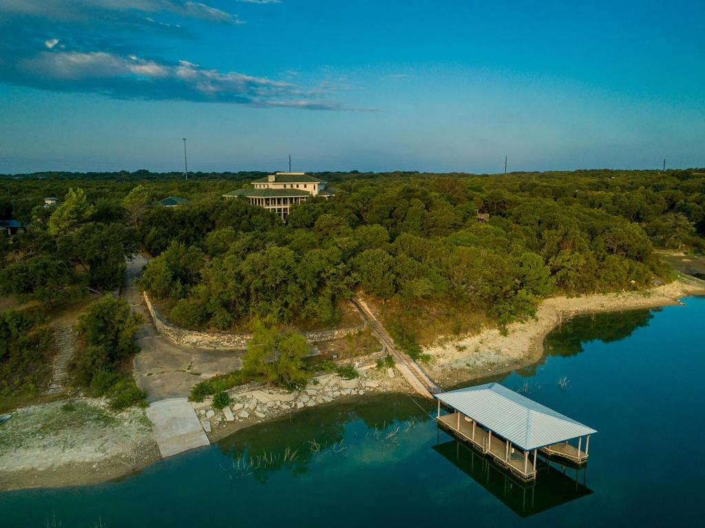 5.41 ac Lake Travis waterfront: private dock, large boat dock & breath taking estate home. Home construction has ceased, buyer to employ their own architect, builder or engineer. Care has been taken to create usable parking & access at the waters edge. Truly unique construction! Photos taken 9/20 at 674.14 lake level.Restrictions: Yes