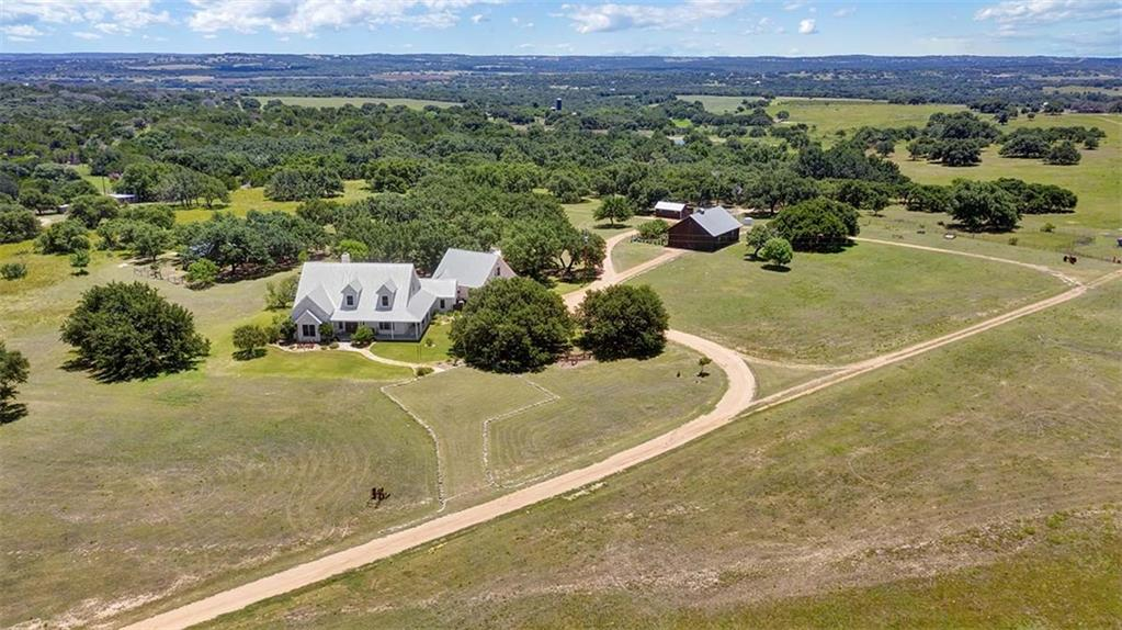This highly improved ranch is showcased by premium forever views overlooking the Pedernales River Valley near Stonewall, Texas. Outstanding main home, an authentic log cabin guest home, 1,600+square foot cedar barn, and other outbuildings. Excellent improved land and great location for winery, vineyard, venue, or residence.Guest Accommodations: Yes