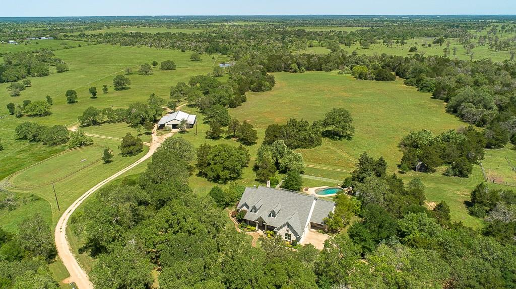 Welcome Home to Turkey Track Ranch! ~ This incredible, custom 4,266 sf home has many architectural details, high ceilings & features 3 bedrooms on the main level, 3 1/2 baths, an office, music room, large bonus room/4th bedroom, screened porch & pool. Surrounded by 102+/- breathtaking, gently rolling acres with many large oaks, a pond & equestrian facilities, all within 45 minutes of Austin. Sprinkler Sys: Yes.  Seller solicits a buyer interested in preserving the current rural homestead nature of this lovely tract and is prepared to negotiate deed restrictions with buyer that serves this end. You don't need horses or cows to appreciate this paradise for all ages & enjoy the peaceful country lifestyle.