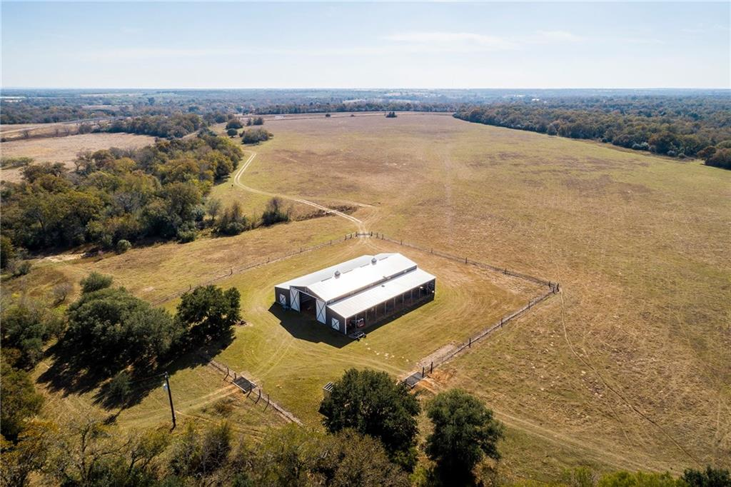 137+ acre ranch move-in ready! 2 ponds, seasonal creek, pecan, post oaks, mesquites. 130 ac surrounded by high game fence, includes 200 inch class Whitetail genetics. 8000 SF barn built in 2012 w/2000 SF 2/2 barndominium. Wide open kitchen & living area. Barn area 4000 SF wide open for farm equip, etc. 18 ft sliding barn doors. 50-amp & 30-amp RV electrical outlets. Also, 2000 SF lean accessible from outside barn. 4.5 ac w/low fence working area joined by cattle holding pens. 300 ft well drilled in 9/2012
