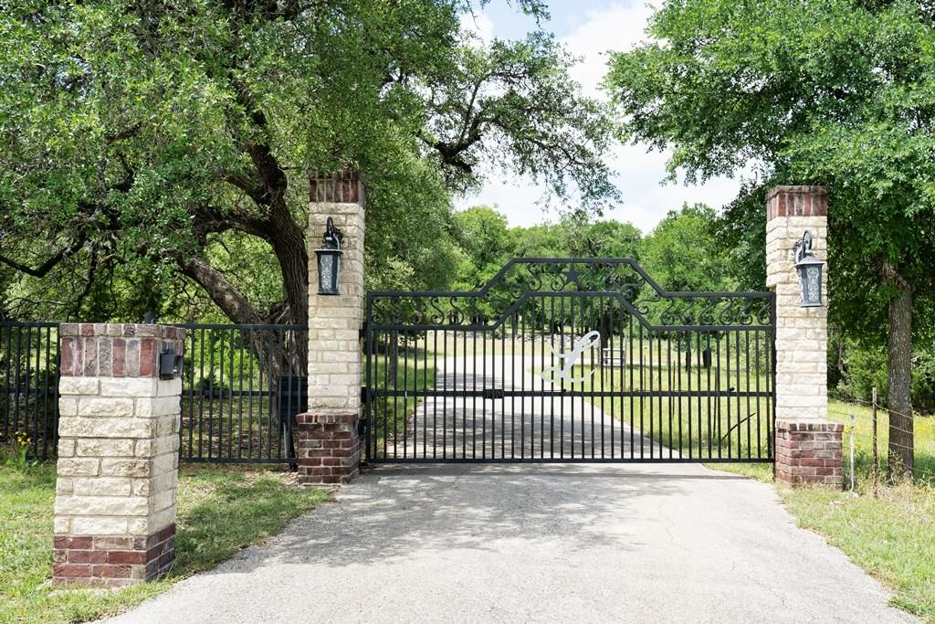 Wrought iron gate with winding paved drive leads through the beautifully treed 8 acre estate. In the heart of Liberty Hill this home has the ultimate of privacy. Boasting 5 beds, enormous game room, separate media room, soaring ceilings, butler's pantry, outdoor living/kitchen, Texas sized master & secondary beds, this truly is a one-of-a-kind property. Ample parking for all the boats/RV/toys, 1200+/- sf workshop, safe room in oversized garage, & so much more. Convenient to major highways and shopping!Guest Accommodations: Yes Restrictions: Yes