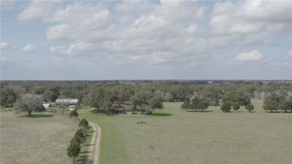 Beautiful working ranch situated on the north side of I-10.  Property has approximately 1700 ft. on Hwy frontage/I-10 Interstate.  Property has cleared open pastures and areas that are heavily wooded with large oaks and tall cedars.  Seasonal creek runs east to west through the middle of the ranch.  Two homes on the property, barn, workshop, working pens, and RV hookups.  Beautiful place to live or a great investment property approximately an hour drive to Houston.