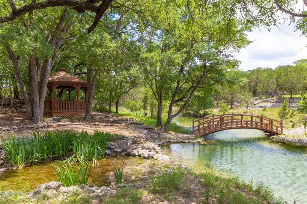 With two residences providing several options, this 10+ acre gem offers beautiful Hill Country views with a creek side gazebo, custom bridge, and provides the perfect place to unwind. A state-of-the-art rainwater collection system includes 30,000 gallons as the primary water supply to the property. Well water also on site. Property has main residence (3/2), a guest house (3/2), and a small 500 sq ft cottage for 3884 sf total living space. Escape from city life. Guest Accommodations: Yes