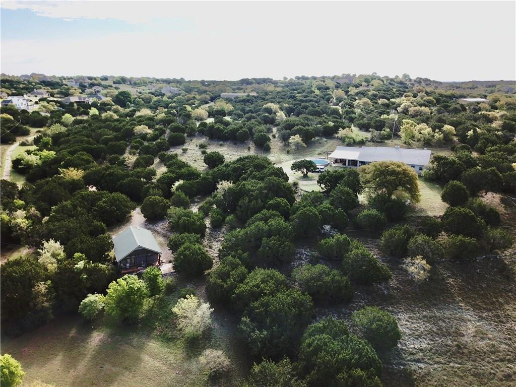 36.883 Acres in high-growth Dripping Springs! 1 mile off Hwy 290 & near Belterra commercial. Use as private ranch, or develop. Multiple build sites. How about a new brewery location?! Limited restrictions in the ETJ! 60' wide driveway leads to the set-back acreage. Existing structures; 2700/sqft main home w/ converted garage as guest suite. (4 BRs, 3 Bath total.) Detached 700/sqft cottage w/ full kitchen, bath, living/dining, and bedroom. B&B income potential! Wildlife Exempt in place means LOWER TAXES.Guest Accommodations: Yes Restrictions: Yes