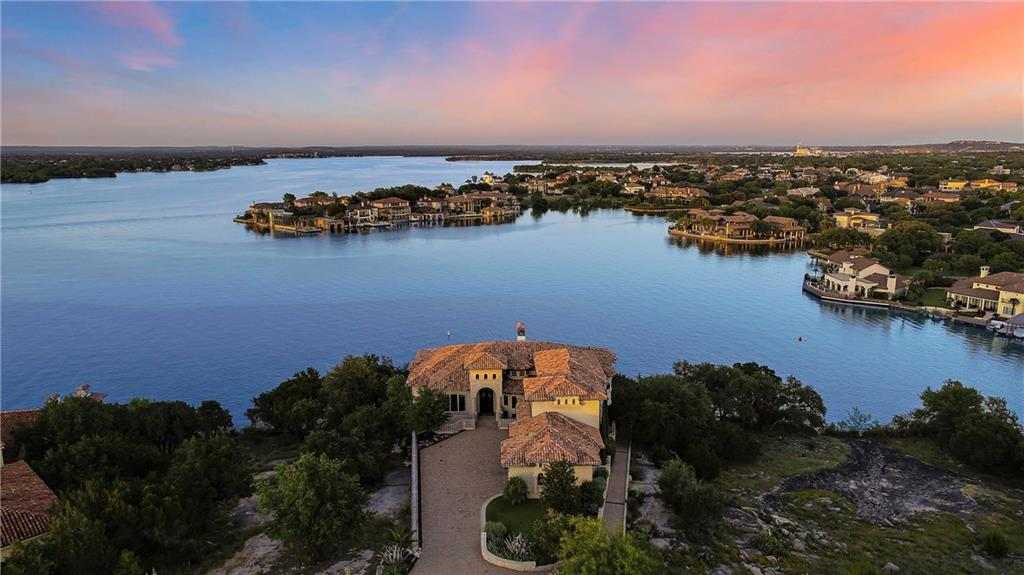 1313 Apache Tears /// Lago Escondido /// Horseshoe Bay, Texas Undeniably one of the most exquisite estates on Lake LBJ, the true epitome of luxury. Stunning lake views for miles, views that captivate the imagination, views overlooking the spa and negative edge pool that seem to flow endlessly into the lake. Several fantastic entertaining areas, patios, balconies, sunning areas, secret garden and fountain, outdoor kitchens and bars, swim up bar, fire pit, lakeside deck, all encompassing, 3500' sq. ft. of travertine decking on 4 different elevation levels and all embracing the unsurpassed views of Lake LBJ. So much more than a home it's a lifestyle, membership to Escondido is included. Entry into the home first revels aye-inspiring lake views through the 24' floor to ceiling butted glass windows,then your eye catches the high vaulted wood beamed ceilings, the hand-crafted iron railing & banisters to a spiral staircase where onyx fixtures adorn the massive chandelier. The home features 6792' sq. ft. of pure luxury and timeless architectural detail, mesquite hardwood and natural travertine stone flooring underfoot while a rich color palate of faux paint, venetian plaster and custom wall finishes eloquently tie it all together. A private estate in the exclusive & secure waterfront gated community of Lago Escondido within Escondido Golf and Lake Club, a prestigious private club with a superb level of concierge service.