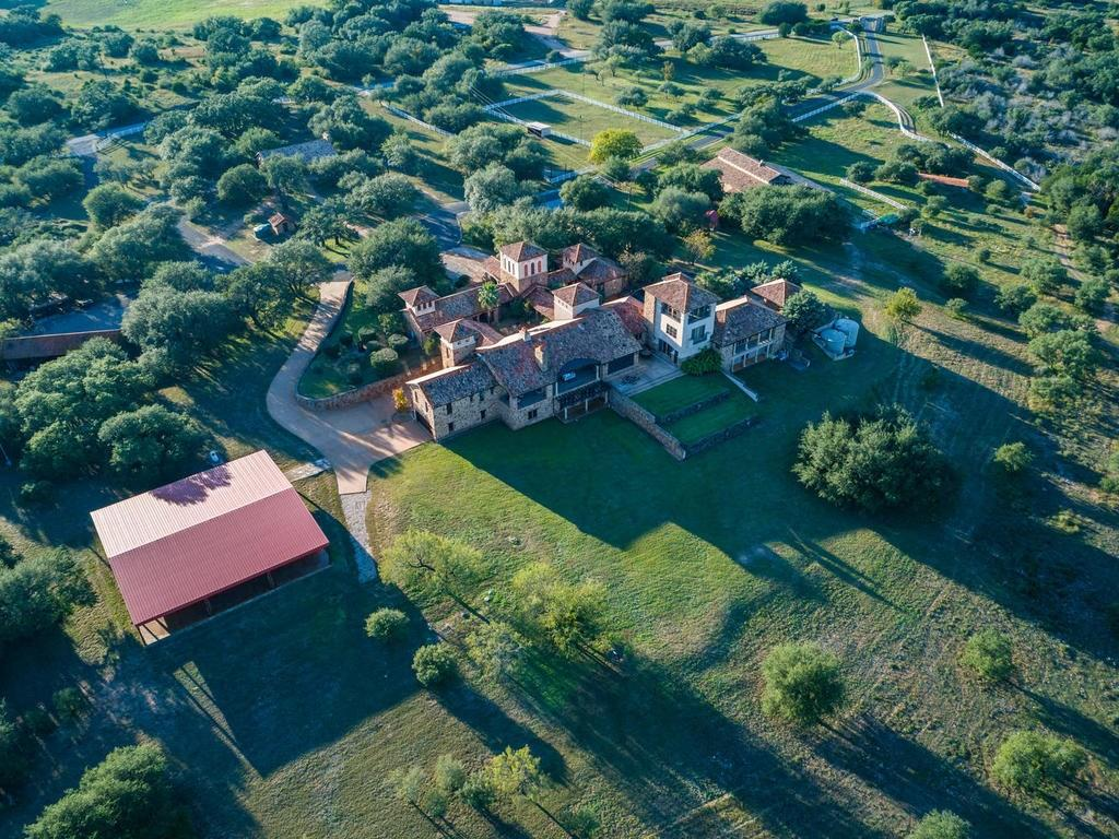 68+ AC Grand Estate w/ panoramic Hill Country views. UNZONED Wildlife Exemption & NO HOA. Main estate w/ 2 separate Guest Casitas, Guest House/Barn & Foreman's house. 7 Car Garage. 3 level resort style pool & koi pond, 2 rain collection systems. Chef's Kitchen w/large casual dining area. Covered porches/decks great for entertaining. Lighted riding arena & 75x75 covered pavilion ideal for large gatherings. 4 Horse stalls. Fall Creek on two sides. See agent for tax rate. Within 1 hr to Austin airport. Sprinkler Sys:Yes
