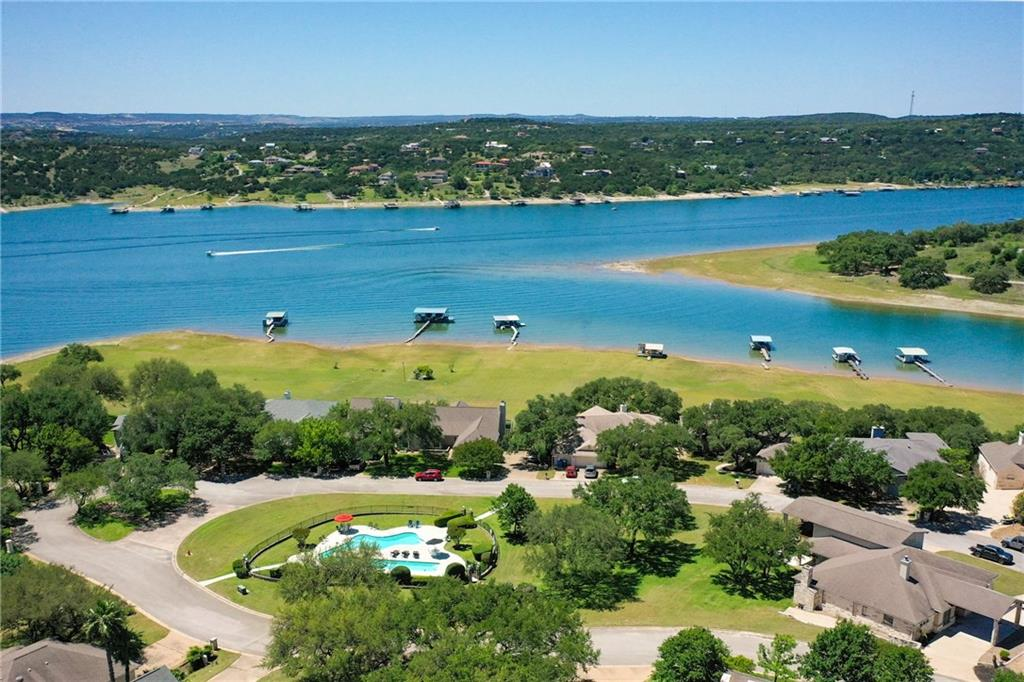 Spectacular waterfront home with gently sloping yard & exceptional views. Located in The Cove, a quiet neighborhood on Lake Travis.  This home features five bedrooms including two master suites, an office, an unbelievable game room & four full baths. Exceptional craftsmanship throughout with wood flooring, granite countertops, and alder wood doors and cabinets.  The upper balcony, covered patio & open patio are perfect for entertaining or relaxing.  Two community pools, exclusive to residents of The Cove, are just steps away.  Many furnishings may convey.  Welcome to Lake Travis living!  No vacations rentals allowed, minimum lease length in the neighborhood is 31 days.  Video link: https://vimeo.com/414924839