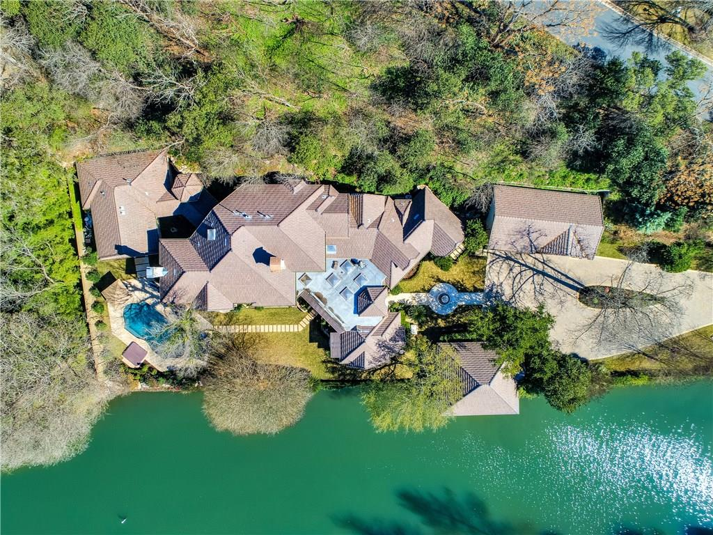 Imagine your own private waterfront oasis in the prestigious gated community of Watersedge. This estate embodies a relaxed, resort-like lifestyle on 300' of Lake Austin's shoreline. Renovated in 2018 with 2 master suites, 4 bedrooms with en suite baths, well-appointed kitchen, media & exercise room, detached guest house, & a breezy covered courtyard with outdoor kitchen. A 2-slip boathouse with lifts & sparkling pool/spa with Lake Austin as the backdrop is the secret sauce to this lakeside lifestyle.Guest Accommodations: Yes Restrictions: Yes  Sprinkler Sys:Yes