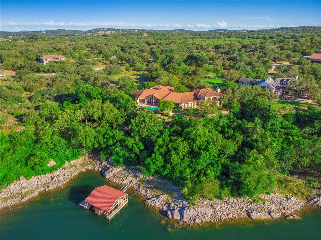Lake Travis waterfront home in a gated community on almost 3 acres. Custom Mexican tile, hand-cut flagstone flooring and beautiful wood cabinetry, windows and doors. Open kitchen offers poolside access. Main level luxury suite with stone fireplace, private pool access and amazing views! Huge master closet with storage. Guest quarters includes living, kitchen and bedroom plus 2 fireplaces. Negative edge pool/spa overlooking the waters of Lake Travis main body. Boat dock with 2 slips + 2 water craft lifts.FEMA - Unknown Guest Accommodations: Yes Restrictions: Yes  Sprinkler Sys:Yes