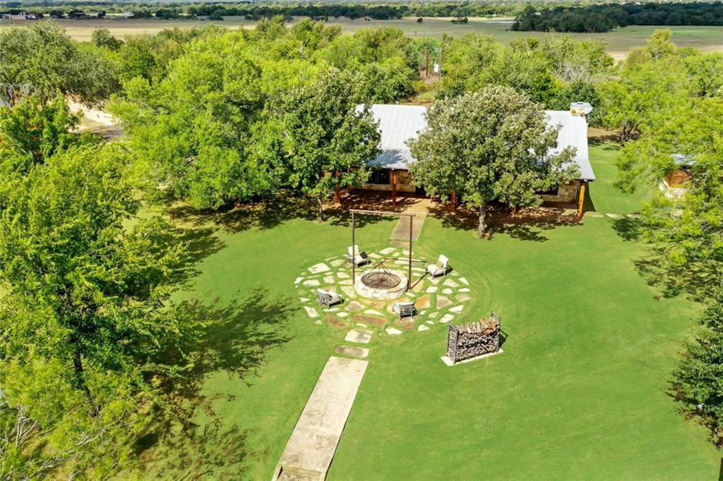 Formerly the Magnolia Country Club, this 1930's ranch home sits on a sprawling 227 (+/-) Acre ranch. Fully restored with all the modern conveniences in 2012. Red aromatic cedar accent wall, wood burning stone fireplace, and stained concrete floors throughout. The kitchen offers, 6 burner gas cooktop, SS appliances, and concrete countertops. The ranch boasts 4 water wells, 2 are solar, 4 stock ponds, 2 barns/shops, heritage oak trees, and fruit orchard. Ideal for hunting, fishing, and amazing star gazing.Restrictions: Yes