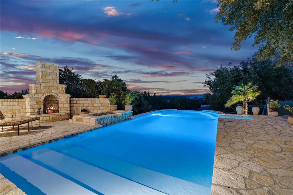 Private gated 20 ac Hill Country Estate, a real slice of Texas! Family lifestyle, 10 mins from Hill Country Galleria & Lakeway. Breathtaking Lake Travis/Hill Country views.Low Taxes/Wildlife Exemption/No HOA. Approx 6,300 SF French Country stone home w/separate 2,100 SF 6 car garage building w/storage & work shop. Vegetable garden, chicken coop/goat shed, fenced area. Abundant outdoor living space, negative edge pool & hot tub, outdoor kitchen with built in smoker box. Private Trails & Fair Weather Creek.Restrictions: Yes  Sprinkler Sys:Yes