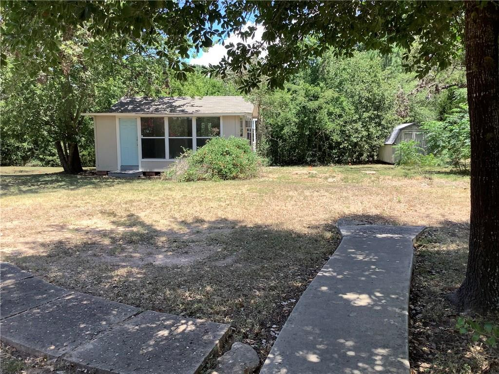 Restrictions: Yes Large lot with Highway 21 frontage conveniently located to downtown Bastrop, State Park and Lake Bastrop.  Improvements include small bungalow, barn, parking lot and utilities.  Great location for small business and room to grow.