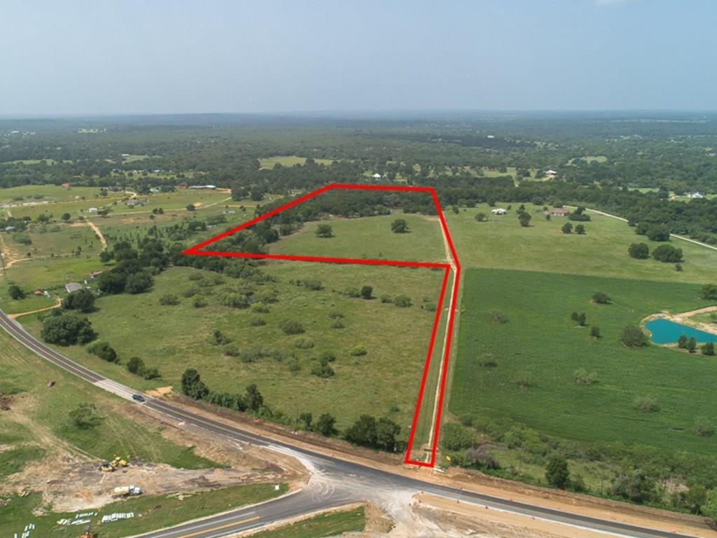 A Little Slice of Heaven! ~ Beautiful 25 acres with park-like setting, gorgeous grove of oaks, trails, pasture, & a stocked pond with black bass & perch. Creek frontage. AG Exemption in place for cattle lease. Aqua Water & Bluebonnet Electric meter present with buried lines ready for your site-built custom home! Property is fully fenced & cross-fenced with mesh horse fencing & has an automatic gate entrance & a proud Texas flag to welcome you. Deeded easement. The shipping container does not convey.Restrictions: Yes