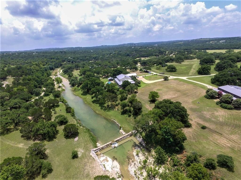 Welcome to Bar Ten Creek Ranch! This 105+/-Acres features a custom 6 bedroom-5 1/2 bathroom Headquarters Home, 3 bedroom-2 bathroom Cottage, 5,000 SF Equipment Barn, & a 6 stall horse barn, plus other pole barns.  The Headquarters includes a custom in-ground pool & cabana overlooking the crystal clear Barton Creek.  Live Oaks, Spanish Oaks, Elms, Sycamore & Persimmon thrive on the ranch. Wildlife Exempt. Gated entrance. Additional land available for a total of 403+/- acres! Other tracts also available.Guest Accommodations: Yes Restrictions: Yes  Sprinkler Sys:Yes
