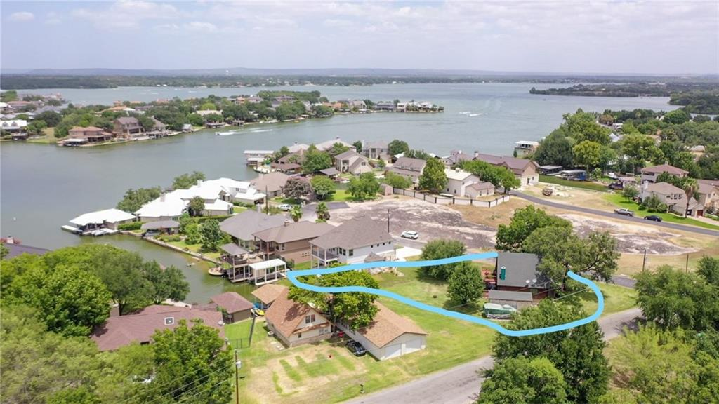 Two story, attractively furnished Lake LBJ log home with a great floor plan. EACH LEVEL has a bedroom, a bathroom, a living area, and a deck facing the lake. A bonus room is upstairs. Exterior features include a covered boat dock with boat slip, seating area and storage room for life jackets, rafts, etc. Grass is watered from lake using lake pump and underground sprinkler. The laundry room is in the garage. Short term rentals allowed. The home is located by the Oak Ridge Estates boat ramp on Lake LBJ.