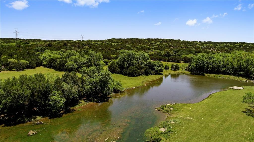 Magnificent high fenced ranch only one hour to Austin. The varied topography gives the land a lot of character and a feel of being bigger than it is.  A seasonal creek meanders through the land and feeds a large pond.   The main home is 3 bedrooms, 2 baths, metal roof, CACH, rocked fireplace with wood burning insert, and Fredericksburg style stone exterior.   The guest cabin has 1 bd/1 bath a large living/kitchen room, & metal roof. Other improvements include a wood frame office, a workshop, metal barn.FEMA - Unknown Guest Accommodations: Yes