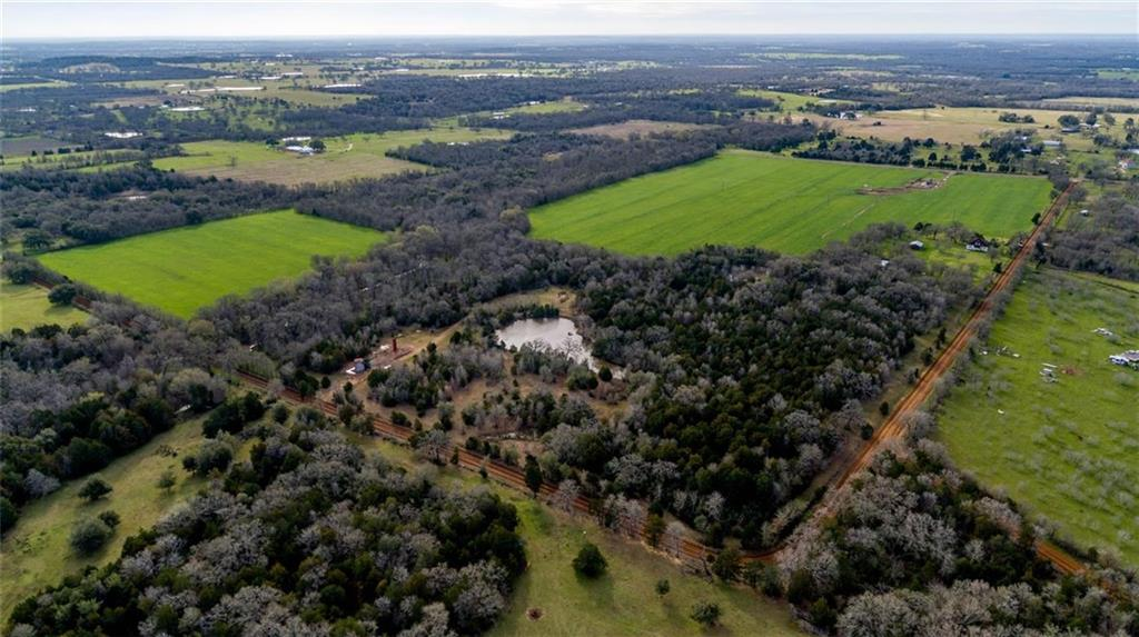 Sprawling green pastures, large ponds, meandering creeks, oak forest, house and utilities - this property has it all! Continue the crop production and cattle grazing, enjoy as a hunting and recreational getaway, or build your dream home and live in the beautiful countryside. The quaint 1,372 sq. ft. features a large front porch and original details. Utilities include county water supplied by Aqua Water Supply Corp, electricity, propane, and a septic tank. Surface sale only; no mineral rights included.Restrictions: Unknown