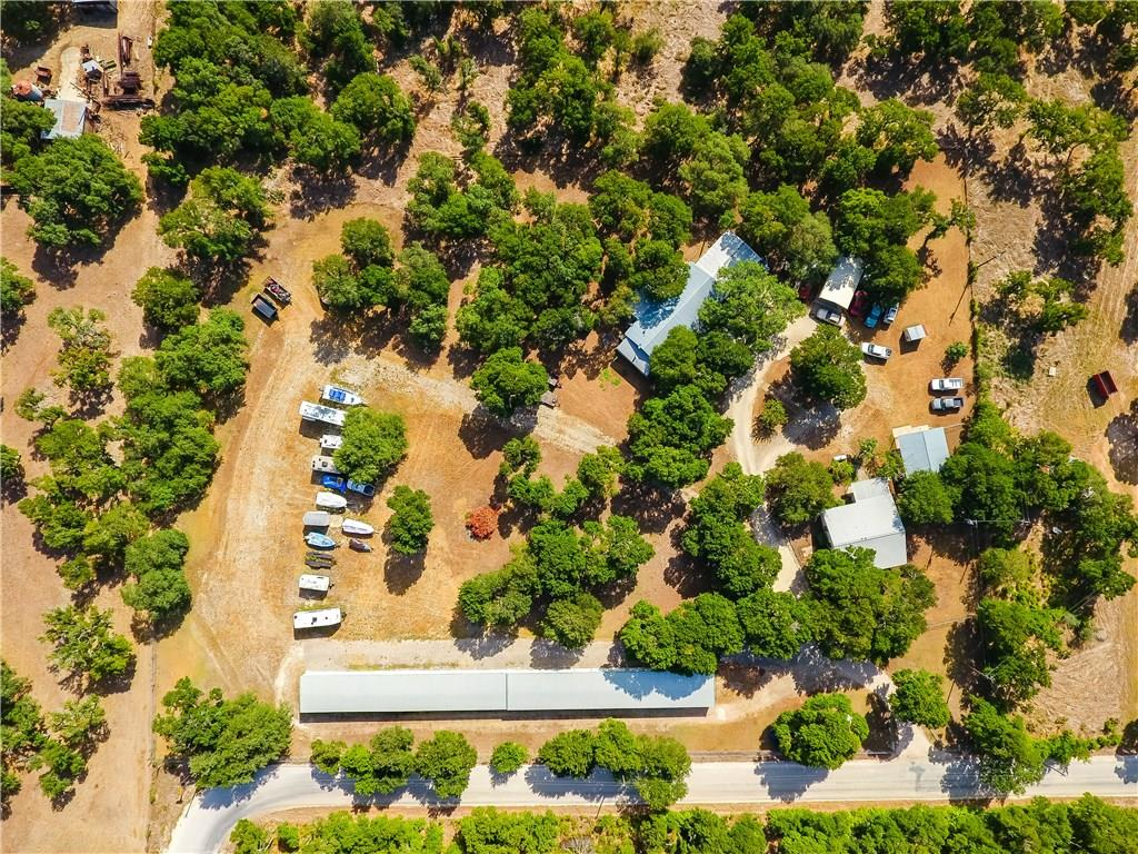 Work where you live on 4.13 acres 2 Homes AND 39 unit storage facility, with RV rental parking. Fully fenced & gated. Awesome treed lot/homes. 2 bed/2bath/1 car carport, updated. Main home larger manufactured home, 2 or 3 bed/2 bath. Set up for office & living! Huge attached steel frame garage/workshop, 2nd workshop & carports. 20+ tons of gravel driveways. Only a short distance from IH 35, convenient location, yet room to roam! Approx.1200/house + 1232sf/mobile homeGuest Accommodations: Yes