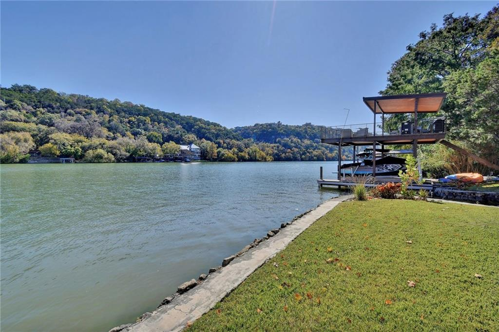Rare opportunity to build on a gorgeous half acre level lot with 100' +/- of waterfront on Lake Austin! 2 Bed | 2 Bath cabin on-site with open living/dining/kitchen concept. A few doors down from Ski Shores and minutes from Central Austin, just West of the 360 Bridge in the coveted Manana West neighborhood. Amenities include beautiful trees, grass flat lot, a private sandy beach cove, modern 2-slip boat dock with jet-ski lift and partially covered party deck. 24hr showing notice.