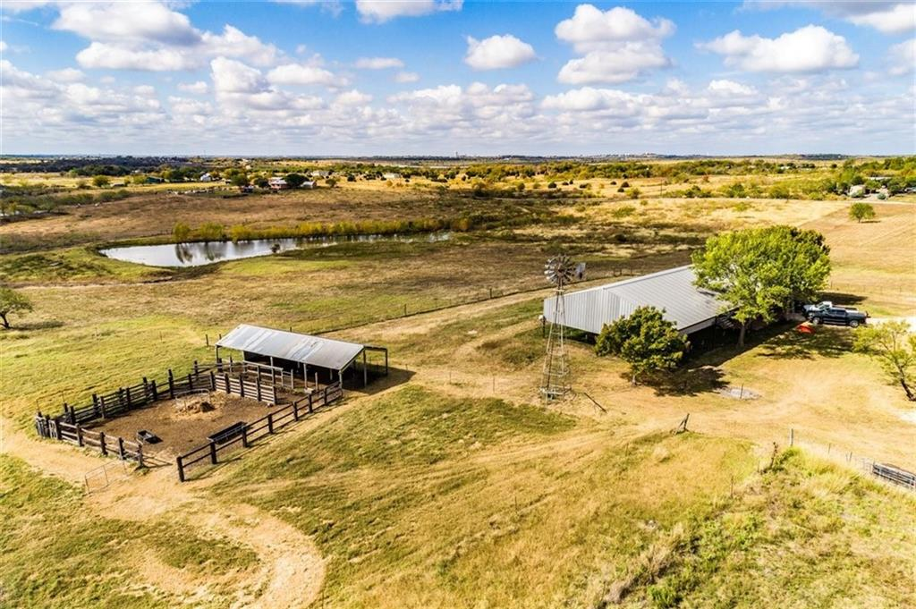 Unrestricted and secluded 27.58 acre track at the end of private road. Small farming opportunity with hay or cattle. Agricultural exemption in place, small pond, single wide mobile home that can be lived in while you build your dream home on the ranch. Completed fence, cattle pen, cross fencing, work shop/storage and endless possibilities with the metal covered structure  measuring 48' x 120', pour concrete floor and enclose it to build a home, workshop, garage, etc.